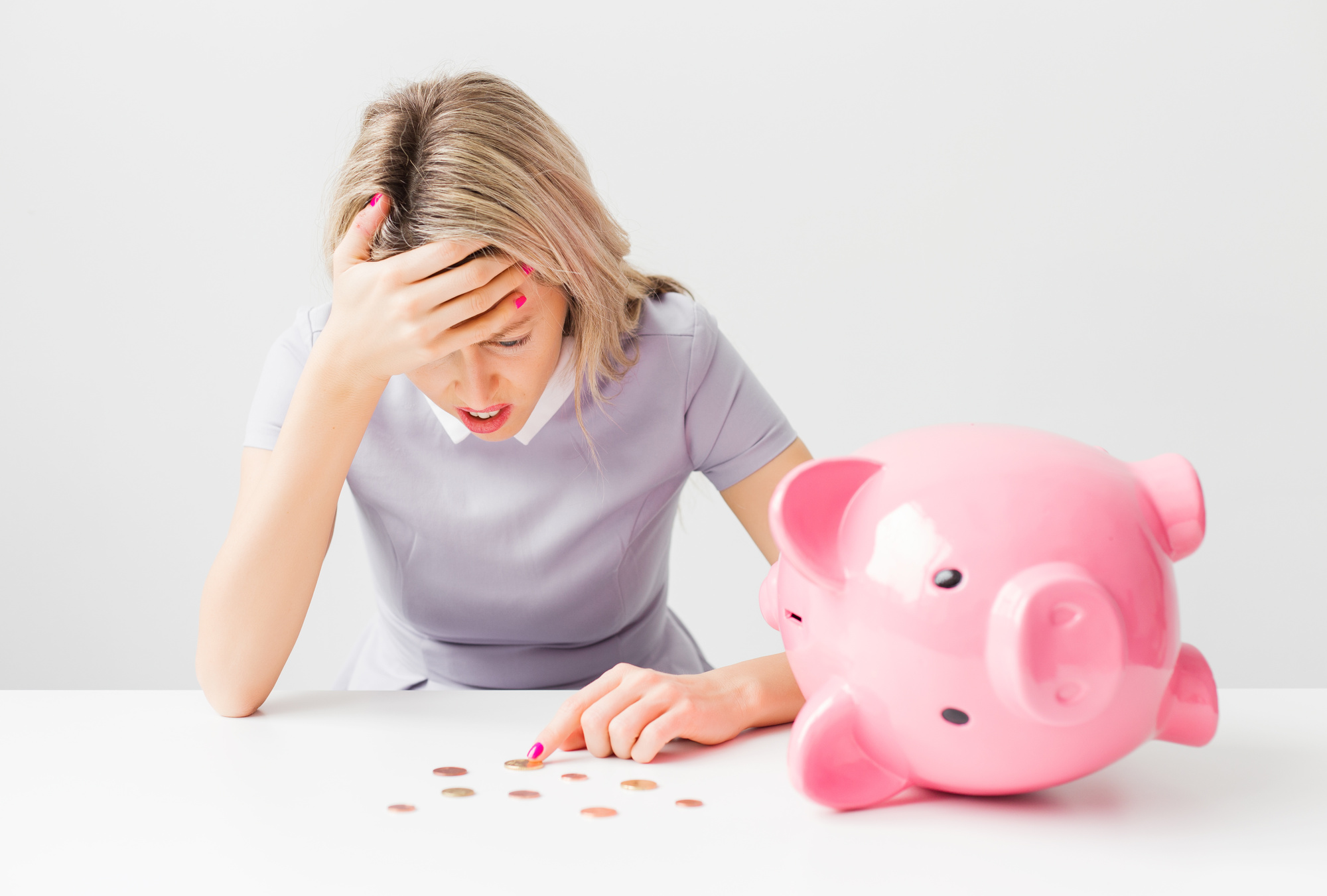 woman counting money from piggy bank